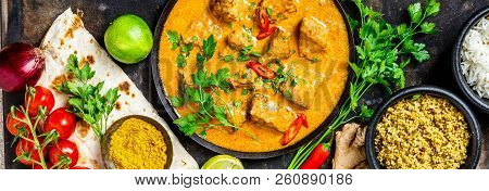 Traditional Curry And Ingredients On Dark Background. Curry, Lime, Ginger, Chili, Naan Bread, Rice,