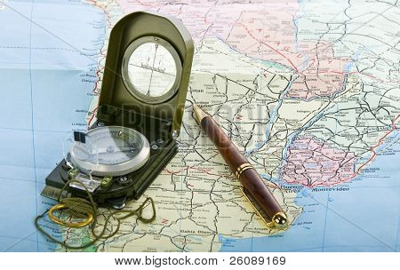 Compass and pen on the map background