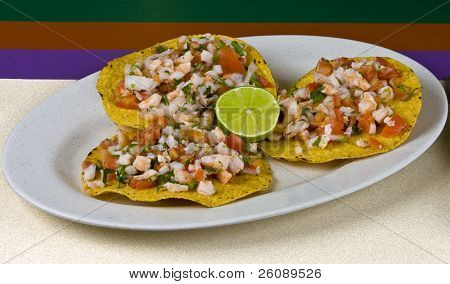 Healthy mexican meal, shrimp tostadas and vegetables on plate