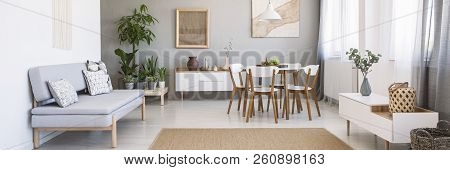 Panorama Of A Bright, Spacious Living And Dining Room Interior With White, Wooden Furniture, Gray So