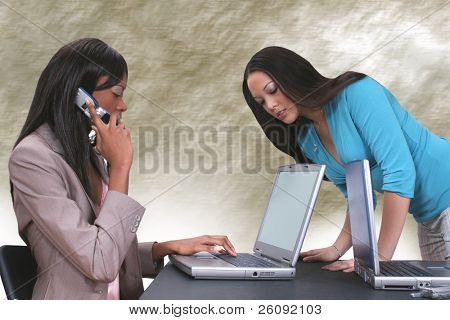 Two beautiful ethnic women working together with laptops at a table.