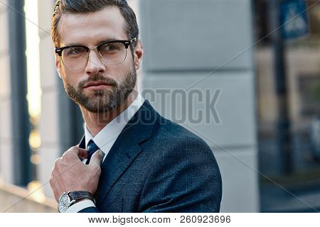 The Young In Spectacles Men Straightens His Tie, His Face Unshaven