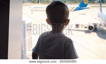 Silhouette Of Little Toddler Boy Looking On Landing Airplane At International Airport
