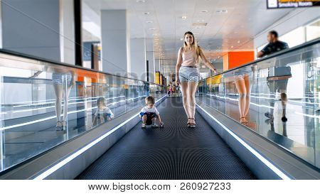 Beautiful Young Woman With Toddler Son Standing On Moving Walkway At Airport Terminal