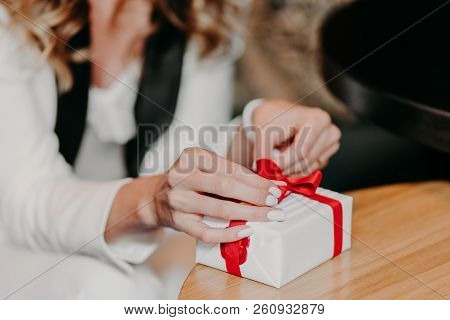 Unrecognizable Woman Ties Presenet With Red Ribbon, Prepares Surprise For Husabnd Or Friend, Has Whi