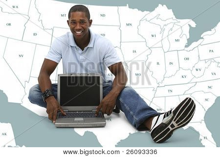Attractive young man sitting on floor with laptop computer over map of US States.