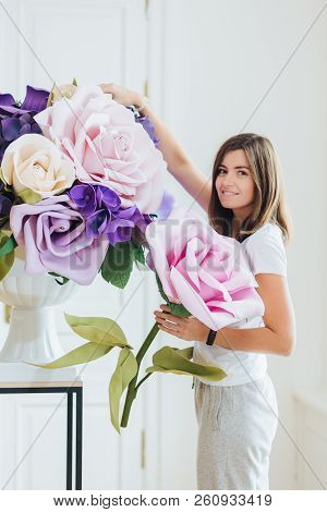 Photo Of Pleasant Looking Female Florist Or Gardener Makes Luxurious Bouquet With Big Roses, Decorat