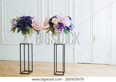 Beautiful Artificial Flowers On Flower Stand, In White Spacious Hall With Doors In Background, Free