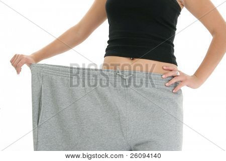 Woman's torso holding out super huge sweat pants to show of weight loss.  Shot in studio.