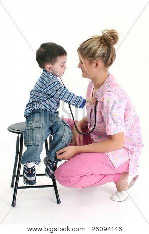Toddler boy listening to nurse's heart with stethoscope.  Shot in studio.