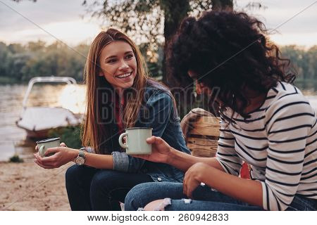 Good Talk With Friend. Two Young Beautiful Women In Casual Wear Smiling And Talking While Enjoying C