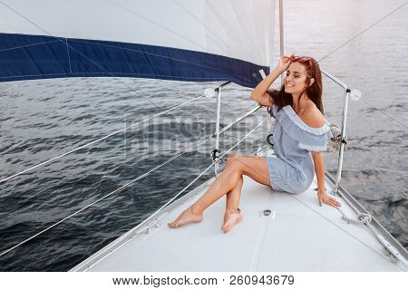 Beautiful Young Woman Sits On Yacht Bowl And Poses. She Holds Red Glasses On Head With Hand And Smil