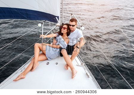 Happy Young Woman Is Lying On Yacht And Point Forward. She Smiles. Guy Sits On Bow Of Yacht With His