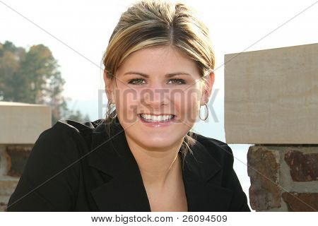 Young woman taking a break out by the lake.  Casual business attiire. Beautiful smile.