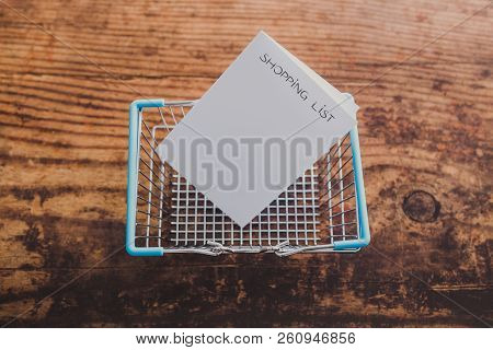 Shopping Basket With Shopping List On Memo Paper And Wooden Surface Background