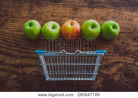 Grocery Store Mini Shopping Basket With One Single Red Apple Among Other Green Ones On Wooden Table,