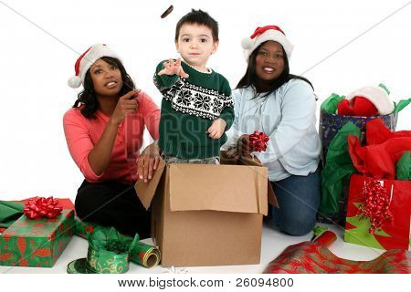 Two beautiful African American woman wrapping Christmas gifts when small boy gets in the way.  Child throwing chocolate mints at the camera.