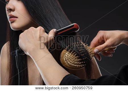 Partial View Of Hair Stylist Straightening Womans Hair With Hair Straightener And Brush Isolated On
