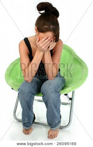 Young woman barefoot in jeans sitting in bright green chair with hands over face.  Shot in studio over white.