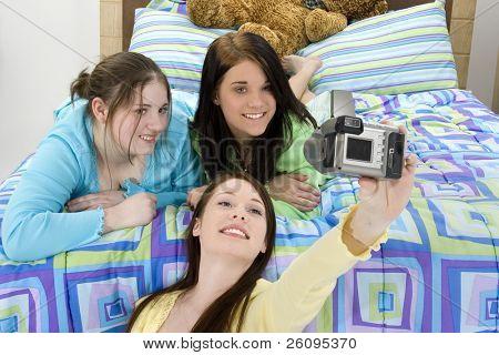Three teen girls taking group self-photo at slumber party.