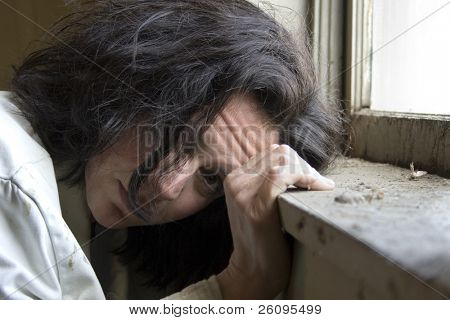 Thirty-eight year old woman looking out the window of impoverished home. Hopeless expression on face.