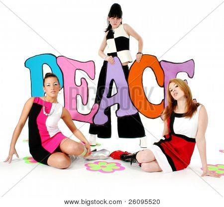 Three beautiful young woman in go-go boots and mini dresses holding colorful peace sign.  60's theme. Shot in studio over white.