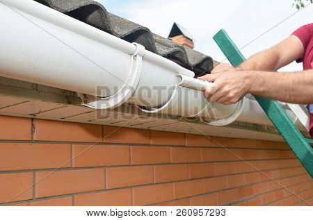 Roofer contractor installing and repair roof gutter. Guttering repair with hands. poster