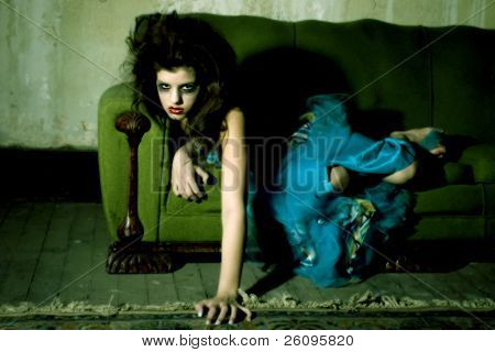 Young girl in goth on old couch.