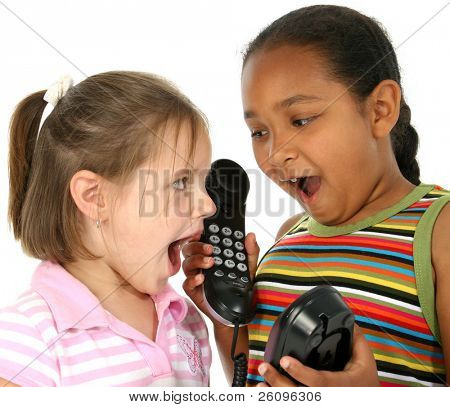 Two six year old friends talking on phone together.  Surprised expressions.