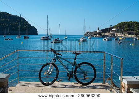 Soller, Mallorca, Spain - September 28, 2018: Bicycle Parked Against Railing In Front Of Moored Boat