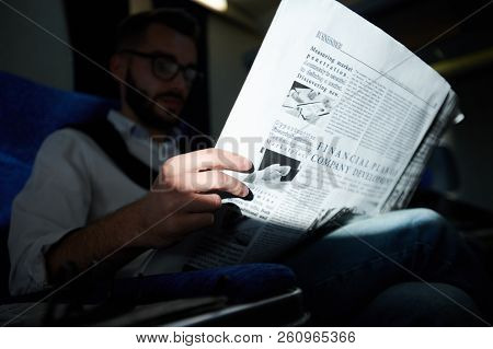 Close Up Of Unrecognizable Man Holding Business Newspaper  While Reading In Plane, Shot With Flash,