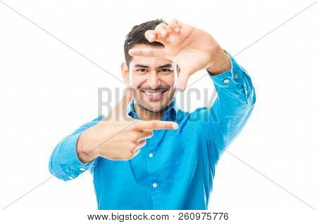 Young Male Making Frame With Hands And Aspiring To Be A Director Against White Background
