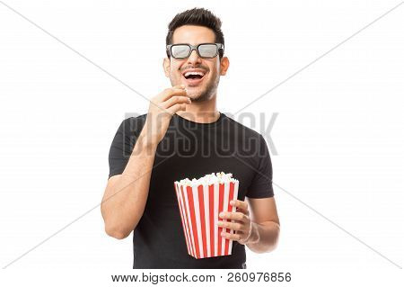 Smiling Young Man Watching 3d Movie While Eating Popcorn On White Background