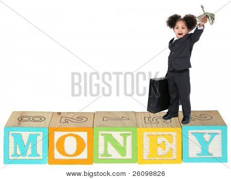 Adorable three year old girl in business suit with money standing on wooden alphabet blocks that spell MONEY>