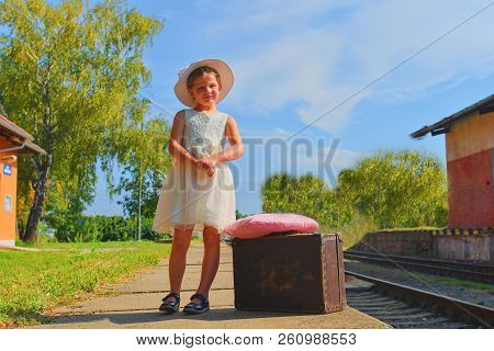 Happy Girl On A Railway Station, Waiting For The Train With Vintage Suitcase. Traveling, Holiday And