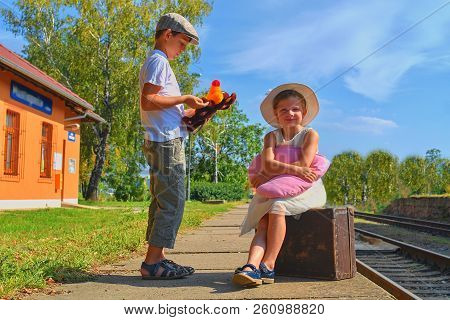 Little  Children - Girl And Boy On A Railway Station, Waiting For The Train With Vintage Suitcase. T