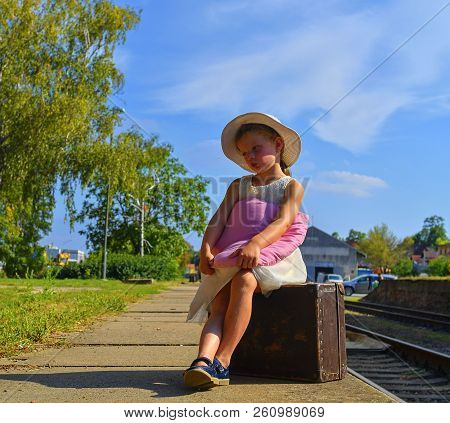 Cute Girl Holding Plush Toy On A Railway Station, Waiting For The Train With Vintage Suitcase. Trave