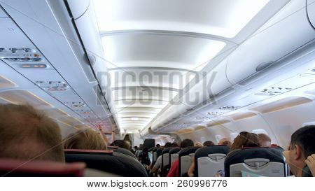 Blurred Image Of Passengers Sitting On Seats And Waiting For Airplane Taking Off
