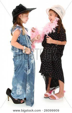 Dos hermosas chicas jugando vestir sombreros y vestidos holgados sobre blanco.