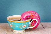 Pink glazed doughnut with colorful sprinkles soaking up coffee from a pink floral cup - conceptualization of a doughnut drinking coffee poster