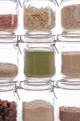 Food ingredient in glass kitchen storage jars. Cookery background image. Studio shot white backlit cooking ingredients. Colorful varied vegan or vegetarian foodstuff for home-baked recipes. poster