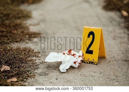Crime Scene Investigation, Bloody Knife With Crime Markers On The Ground, Evidence Of Murder.