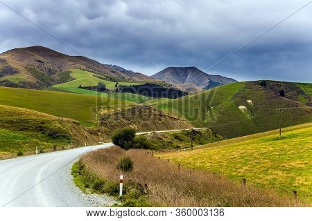 The magnificent landscape of New Zealand. The hills were overgrown with yellowed grass. The road crosses the hills of South Island. The concept of active, environmental, automotive and photo tourism