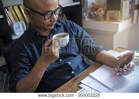 Work From Home Concept. Asian Men Using Mobile Phone And Laptop To Work Online At Home. Businessman