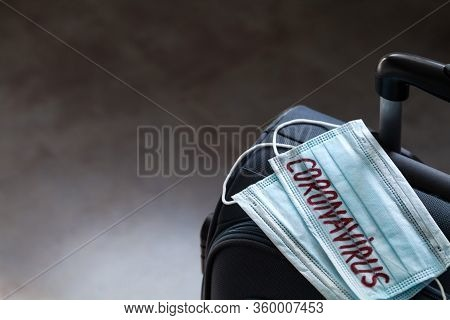 Travel Suitcase And Medical Mask. The Ban On Travel During The Epidemic Of The Coronavirus And The I