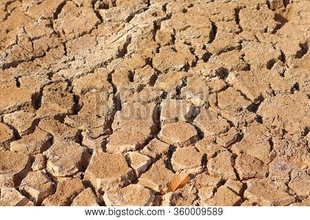 Cracked Soil Textured Background. Cracks On The Dried Soil In Drought Season