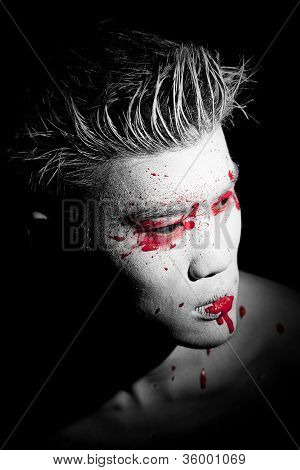 Young asian male with red paint fashion makeup