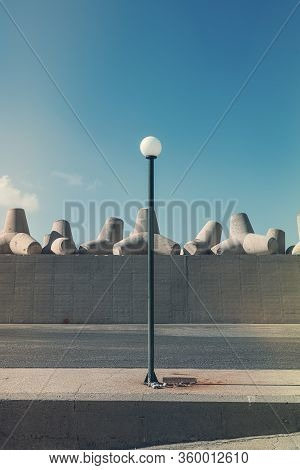 Simple Street Lamp In Front Of Concrete Breakwaters In A Harbor