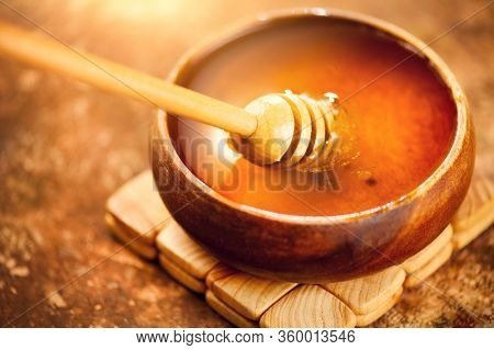 Honey dripping from honey dipper in wooden bowl.  Close-up. Healthy organic Thick honey dipping from the wooden honey spoon, closeup. Top view