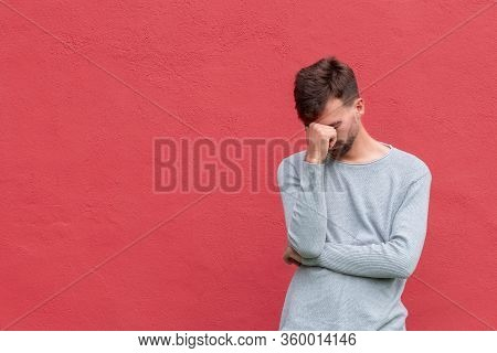 Stressed Young Man Covering Face With Hand. Man On Red Wall Background, Copy Space. Pain Concept.